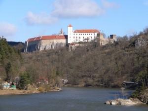 Hrad se tyčí vysoko nad řekou.